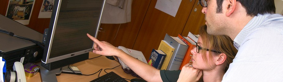 Woman sitting at a desk pointing to a text on a computer screen and a man looking over her shoulder