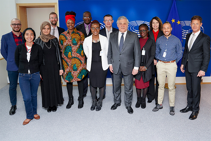European Parliament President Antonio Tajani and the 2019 Sakharov fellows stand in front of an EU banner
