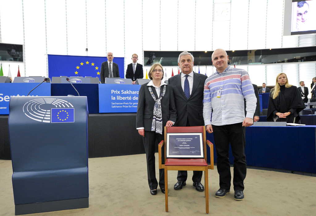 European Parliament Antonio Tajani, Oleg Sentsov's cousin Natalya Kaplan and Sentsov's lawyer Dmitri Dinze stand behind an empty chair in the European Parliament's hemicycle during the award ceremony