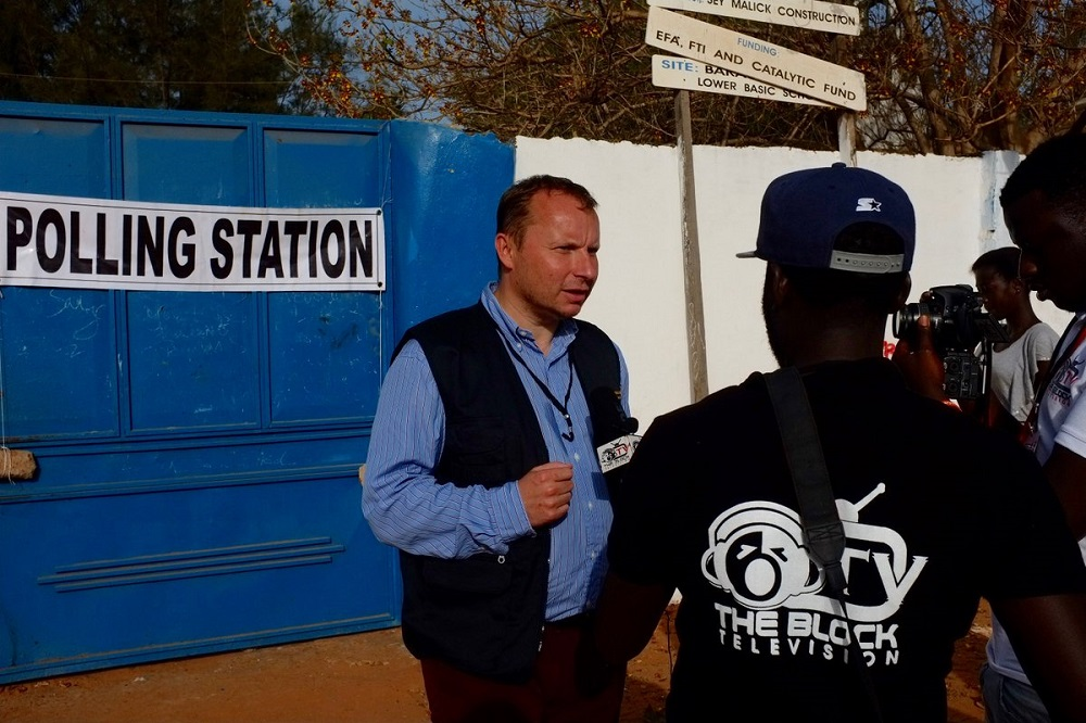 Observer standing in front of the gates of a polling station in Gambia